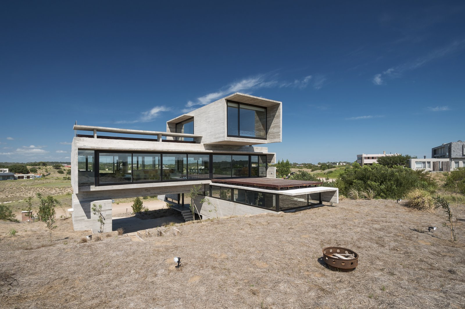 The middle volume is the largest and most transparent of the three volumes. Tagged: Exterior, Concrete Siding Material, Glass Siding Material, House, and Flat RoofLine.  Best Photos from This Stacked Concrete Home Is Not Your Typical Golf Course Dwelling