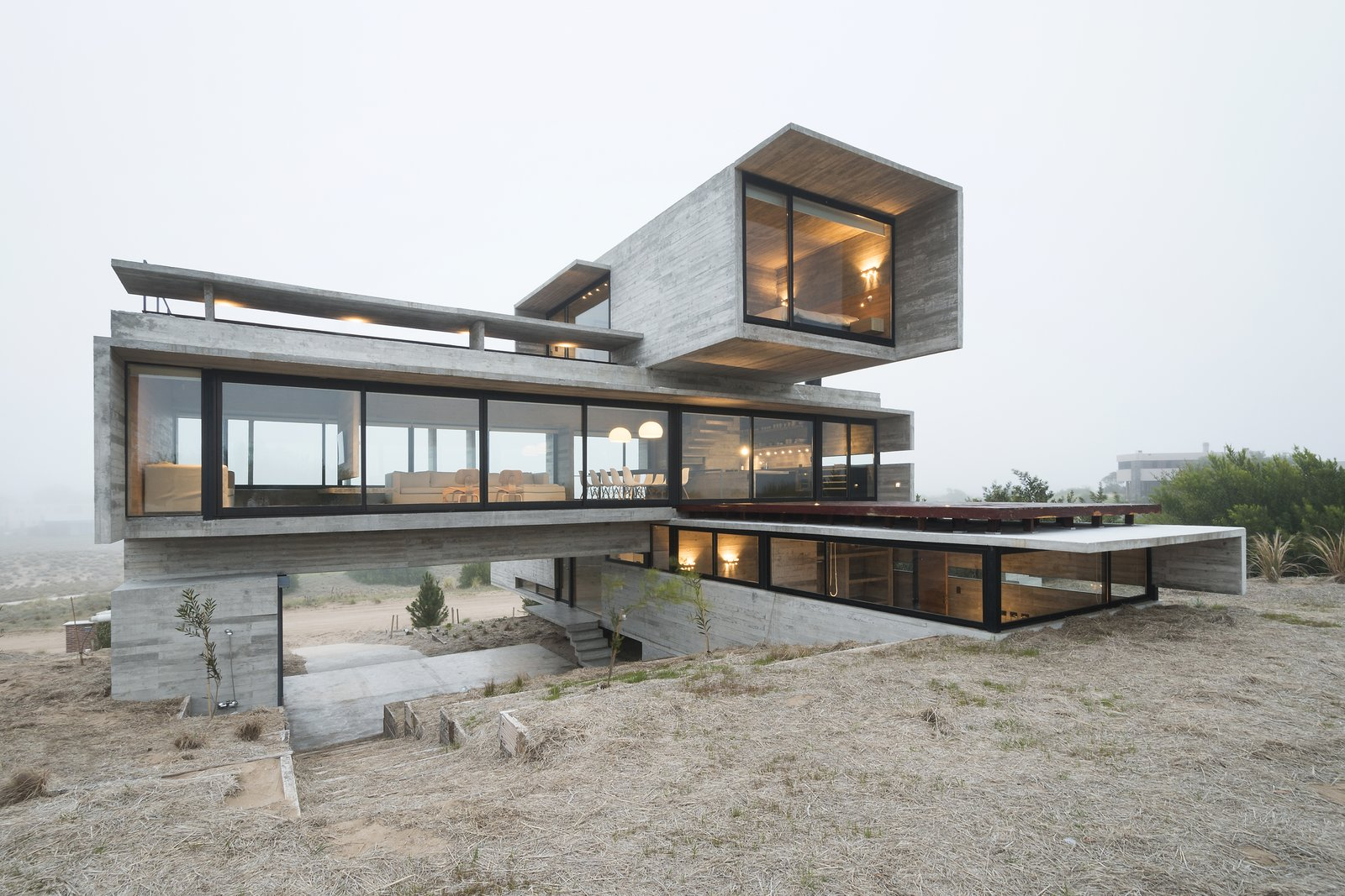 The cavern-like space underneath the middle volume serves as a parking area. Tagged: Exterior, House, Glass Siding Material, Flat RoofLine, and Concrete Siding Material.  Best Photos from This Stacked Concrete Home Is Not Your Typical Golf Course Dwelling