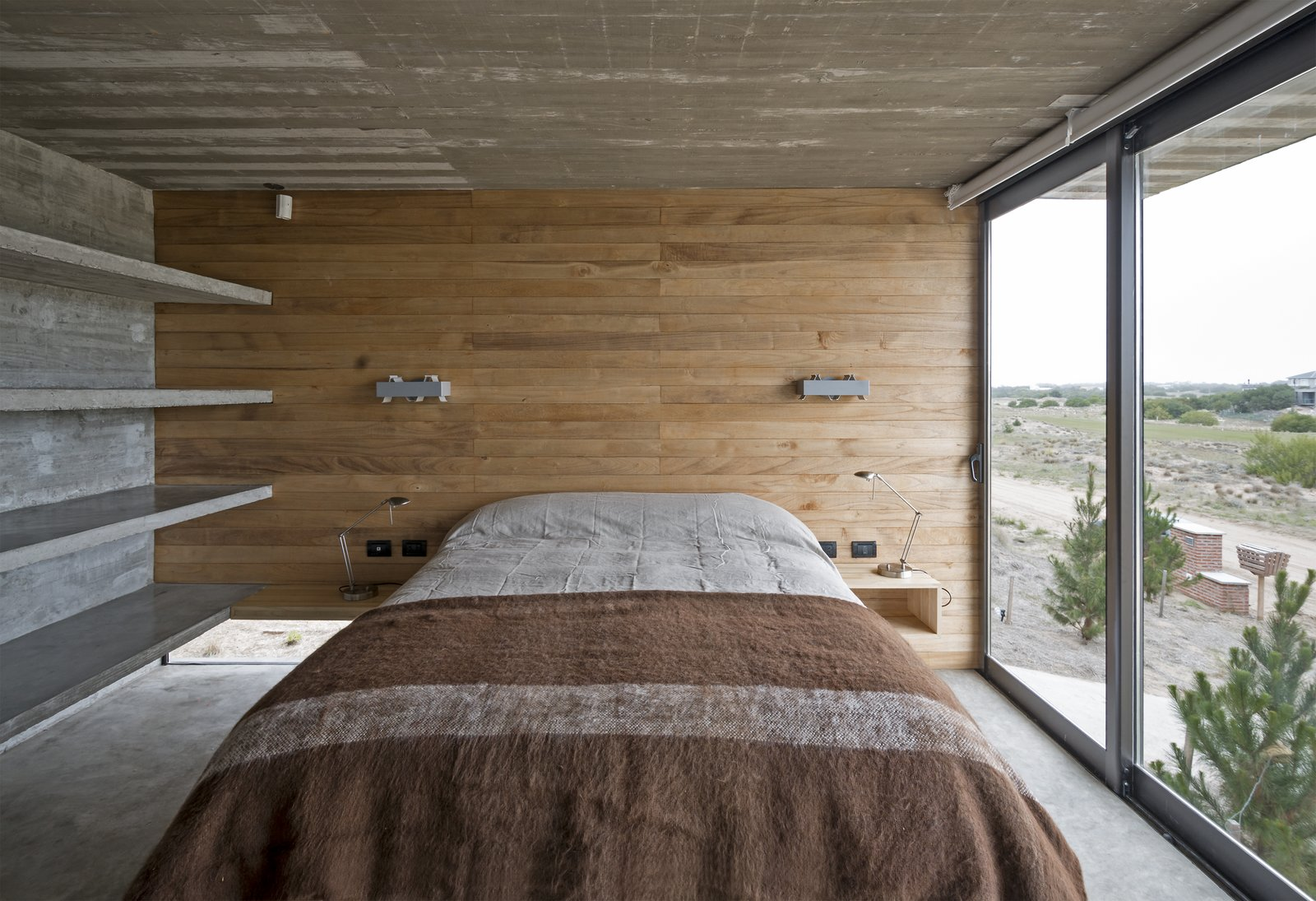 Built-in concrete shelves in one of the guest bedrooms. Tagged: Bedroom, Bed, Shelves, Concrete Floor, Table Lighting, and Lamps.  Best Photos from This Stacked Concrete Home Is Not Your Typical Golf Course Dwelling