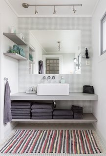 "Relax and Recharge at This Charming Norwegian ""Hytte"" Rental - Photo 12 of 13 - Built-in shelves and an unframed mirror give the bathroom vanity a clean and streamlined look."