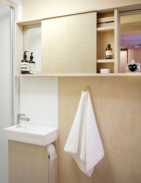 The smartly-designed bathroom vanity supports the sink, and also holds the toilet paper.