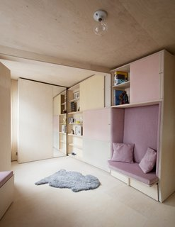This Tiny 140-Square-Foot Apartment Boasts Comfort and Function - Photo 3 of 15 - The cabinet doors slide to reveal book shelves.
