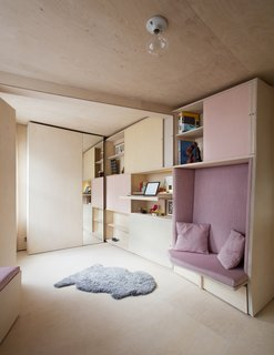This Tiny 140-Square-Foot Apartment Boasts Comfort and Function - Photo 4 of 15 - A pullout desk is hidden underneath one of the shelves.