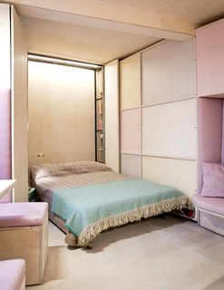 This Tiny 140-Square-Foot Apartment Boasts Comfort and Function - Photo 9 of 15 - A hidden Murphy bed is located along the narrowest wall of the triangular-shaped apartment.