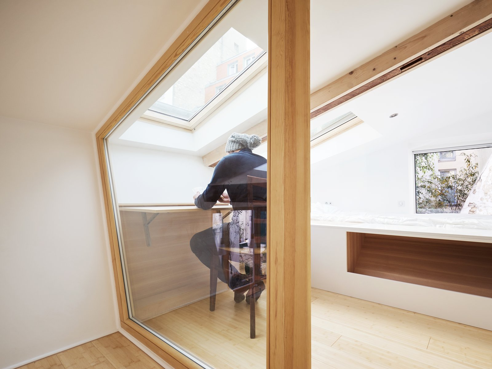 A skylight illuminates the retractable desk in the lofted workspace.