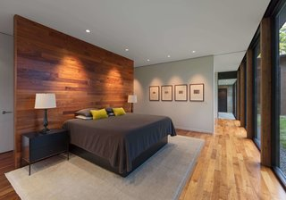 """This Glass House and """"Shiny Shed"""" Merge With Nature in Minnesota - Photo 9 of 15 - In the master bedroom, a wooden accent wall with coat hooks on one side serves as a partition for the bed."""