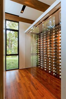 """This Glass House and """"Shiny Shed"""" Merge With Nature in Minnesota - Photo 8 of 15 - A glass-encased wine storage system lets the owners to select specific bottles with ease."""