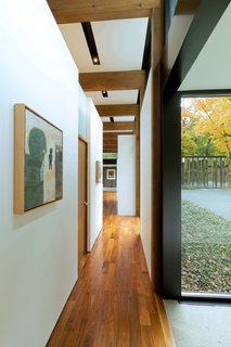 """This Glass House and """"Shiny Shed"""" Merge With Nature in Minnesota - Photo 4 of 15 - Artwork hangs along the walls of the hallway that connect the wings."""