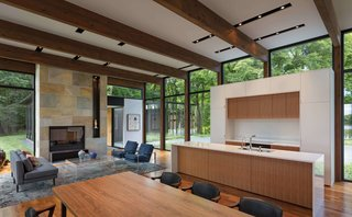 """This Glass House and """"Shiny Shed"""" Merge With Nature in Minnesota - Photo 5 of 15 - The open-plan kitchen, living room, and dining area are located in the largest wing."""