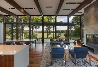 """This Glass House and """"Shiny Shed"""" Merge With Nature in Minnesota - Photo 2 of 15 - The house is sited on a wooded plateau overlooking a wetland and lake beyond."""