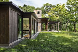 """This Glass House and """"Shiny Shed"""" Merge With Nature in Minnesota - Photo 6 of 15 - A patio with a pergola is accessible via the living room."""