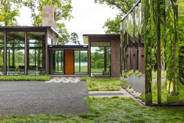 A shiny mirror-clad shed greets guests as they approach the house.