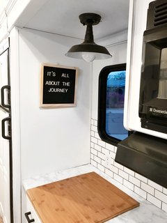 Hit the Road With This Chic Camper on Sale For $28K - Photo 15 of 15 - The kitchen workstation faces a window, allowing for ample amounts of natural light.
