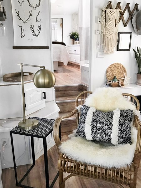 A sheepskin rug, a weave hanging on the wall, and vibrant fabrics add much personality to the small mobile home.