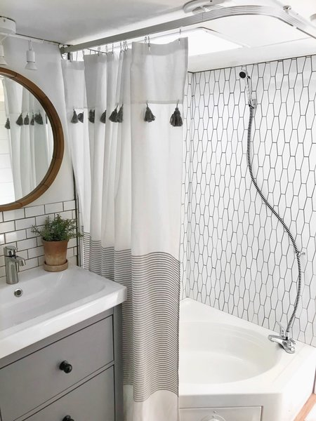 A renovated bathroom with a new showerstall and tiled wall.