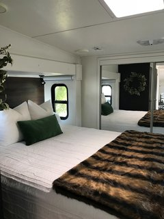 Hit the Road With This Chic Camper on Sale For $28K - Photo 5 of 15 - A skylight window illuminates the bedroom, which appears larger than it is because of the closet with mirror-clad sliding doors.