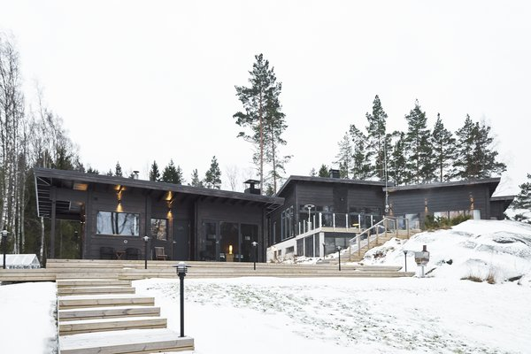 Located on a rocky seaside plot in Inkoo, Finland, this family home designed by architect Katja Jämsä was built with 204-millimeter wide Honka Fusion non-settling laminated timber, and includes large glass windows and doors.