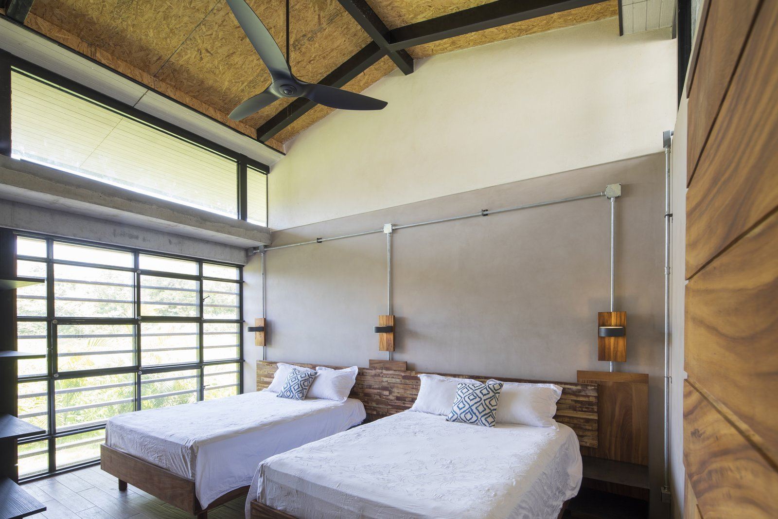 Floor to ceiling glass windows bring the green outdoors into the bedroom.