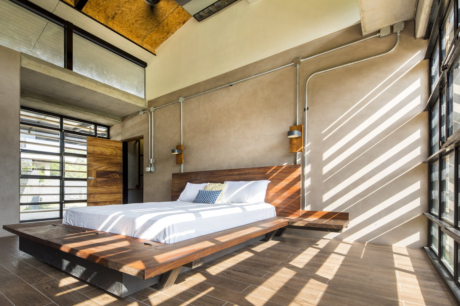 Glass walls are fitted on two sides of the master bedroom.