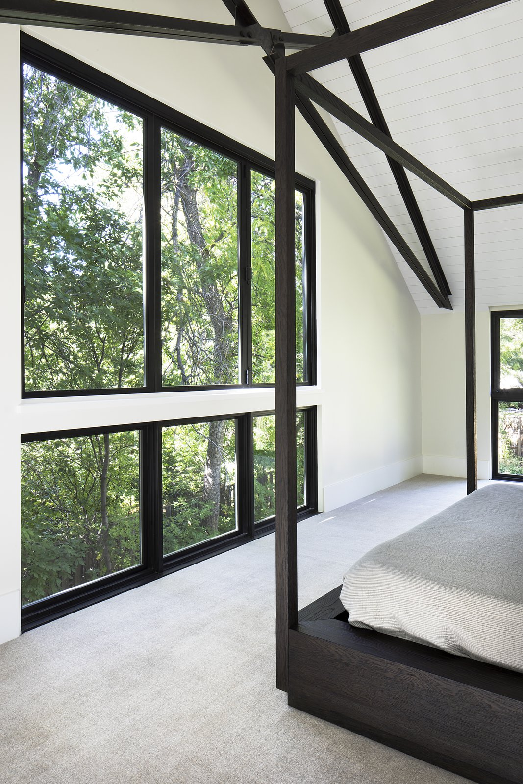 Inspired by historic farmhouses, beams are left exposed in the bedroom ceiling.
