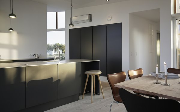 A dark, streamlined kitchen in the open-plan living area.