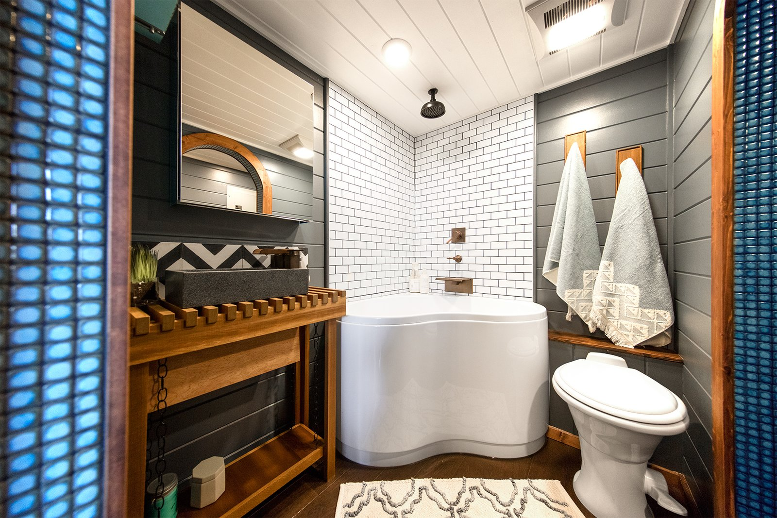 On the opposite end of the dining area is a spa-like bathroom with sliding arched doors, Moroccan tile trimming, a walk-closet, toilet, rain shower, and a corner jacuzzi bathtub.