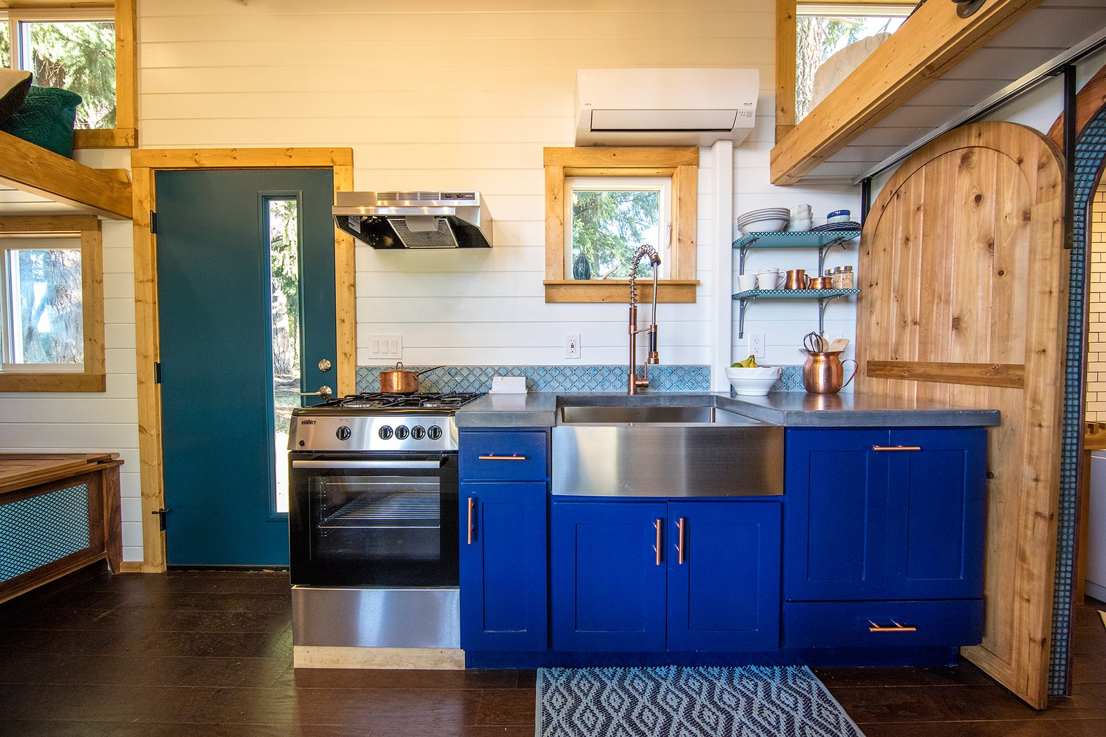 The kitchen has concrete countertops and bright blue cabinets.