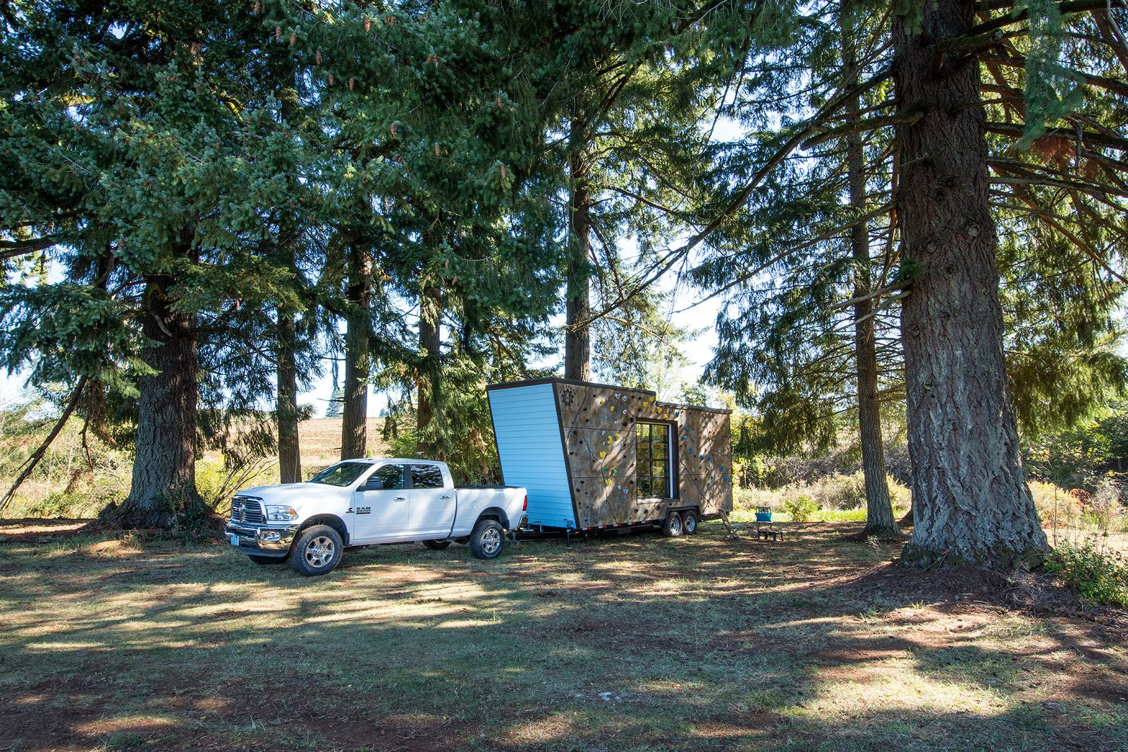 This 28-foot long, towable, double-axle trailer home, has a front façade that's a rock climbing wall.