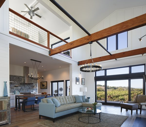 Modern home with living room, sectional, medium hardwood floor, pendant lighting, and floor lighting. Photo  of Modern Vineyard Farmhouse