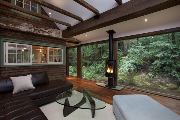 Modern home with living room, medium hardwood floor, gas burning fireplace, and console tables. Photo  of Creekside Cabin