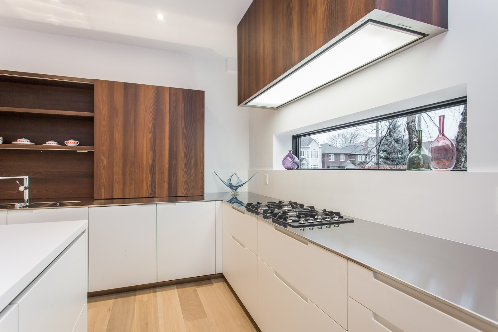 A long window above the countertop provides a nice view to the outside world while cooking.  Manor Road house by Nathalie Thorel