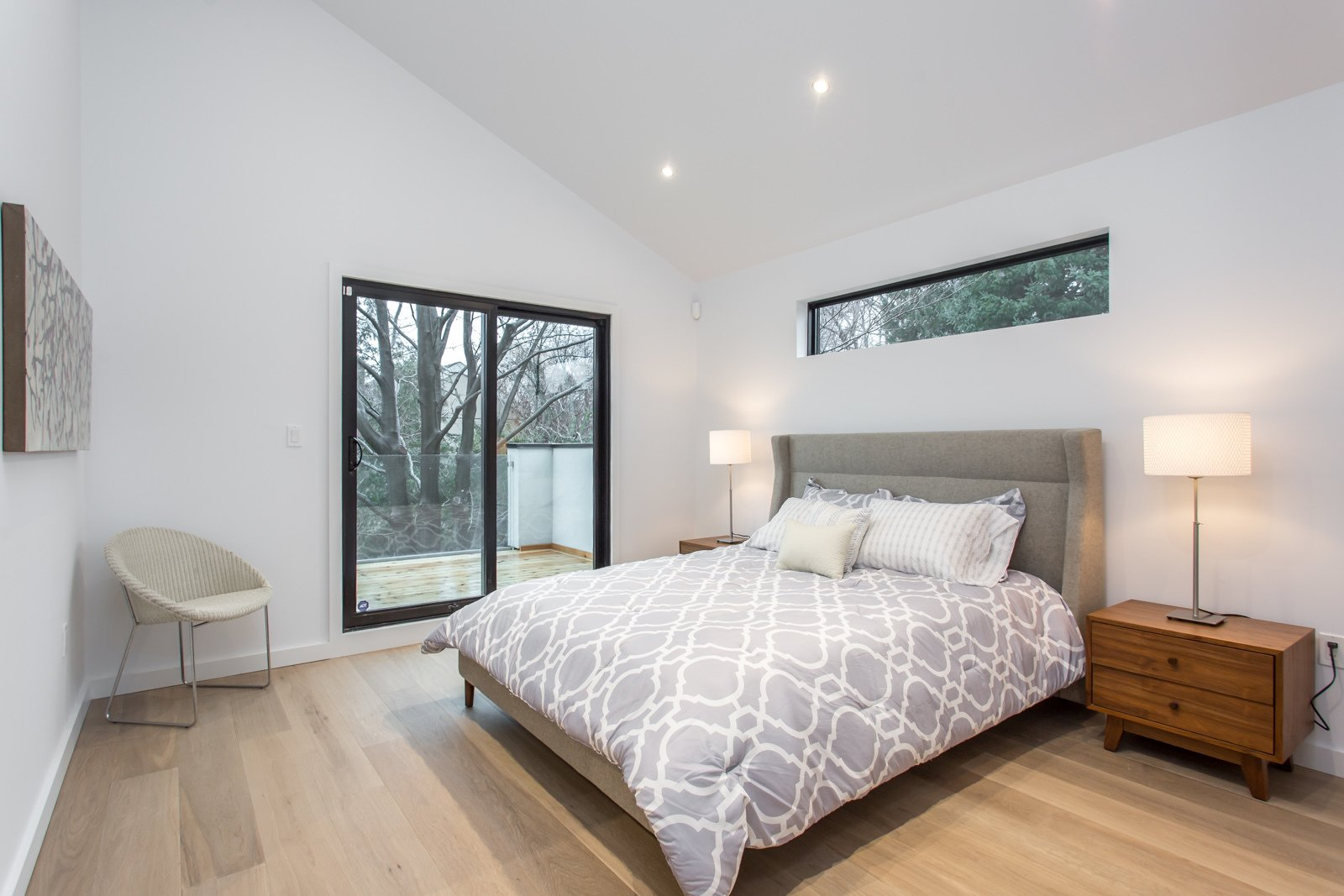 The master bedroom on the second floor with a walk out deck, overlooking the private backyard.   Manor Road house by Nathalie Thorel