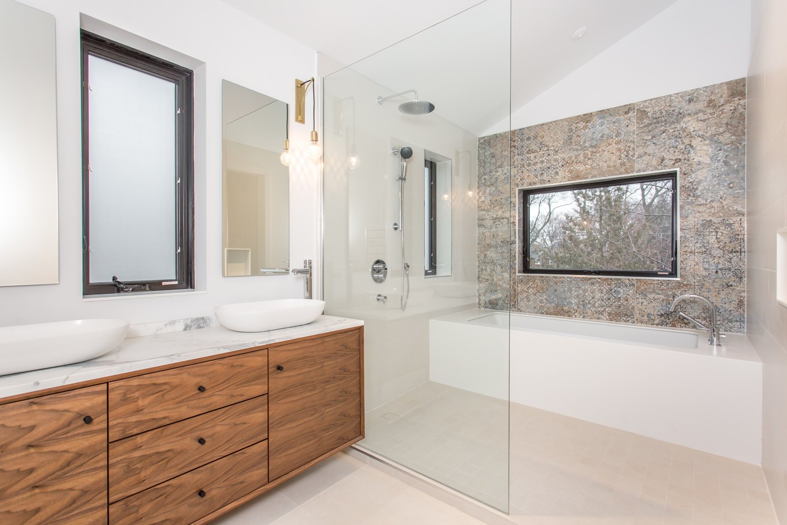 A master ensuite, with a bath/shower area, Vestige pattern tiles from Aparici, marble countertop and a walnut vanity.   Manor Road house by Nathalie Thorel