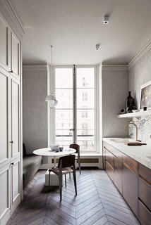 Old-World Charm Meets Modern Finishes in These 6 Parisian Apartments - Photo 3 of 12 - The Paris kitchen of architect  Joseph Dirand features stylish chevron floors in oak and two-tone cabinetry—one paneled with traditional pulls, the other modern and hardware-free—in a light gray and a patinaed brown. An elegant, sculptural faucet and unusual, geometric pendants and ceiling-mounted light fixtures ensure that the space feels modern.