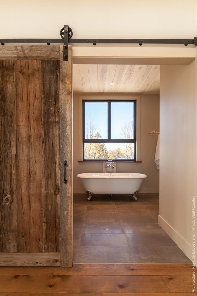 Main bathroom has a very warm feeling created by the raw elements used on the floors, walls and ceiling.  La Maison Hatley by Geneviève Audette