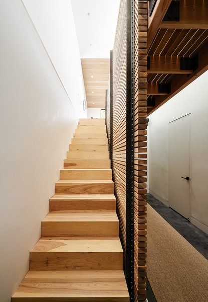 By eliminating the attic and carving out a former crawl space, Red Dot Studio created room for the residents' bedrooms underneath the primary living areas. The slatted-hickory-and-glass bridge allows light from a row of skylights to penetrate deep into the lower level. Photo 2 of A Renovated Tiny Victorian modern home