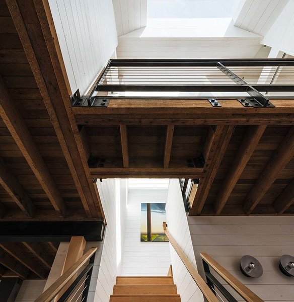 """Modern home with living room. """"Typically in close city lots, all the light comes from the front and back of the house, so that the center becomes a dark spot,"""" Curtiss said, explaining her decision to install a Velux skylight above the staircase. """"[It brought] a glow to the center of the house."""" On the floor beneath it, she cut a hole that ushers in daylight to the lower regions of the house. It also creates a bridge separating the master bedroom from the two smaller rooms. Photo 3 of Space-Efficient San Francisco Renovation"""
