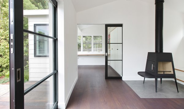 Modern home with shelves, dark hardwood floor, craft room, desk, study, living room, bench, and wood burning fireplace. Photo 4 of A Mill Valley Accessory Building
