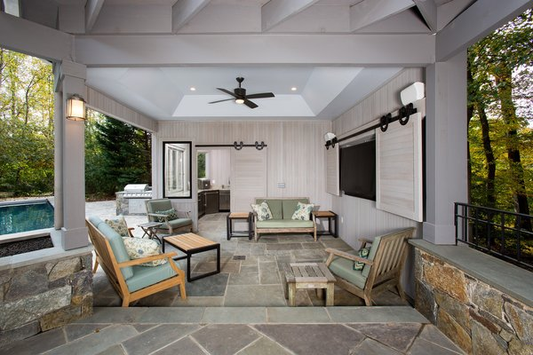 Sun bathers can escape the heat while dining on the flagstone patio under the ceiling fan or warm up while the gas fire pit is operating. see the full case study, http://www.markivbuilders.com/outdoor-kitchen-bethesda-maryland/ Photo 9 of Outdoor Kitchen and Patio modern home