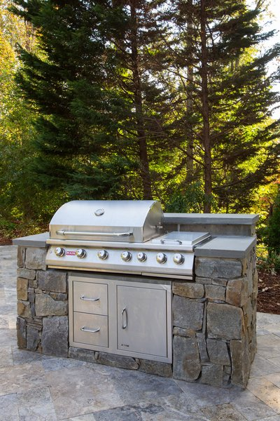 This deluxe professional grill provides amble power to cook for a large group. It includes a side burner, four burners, and storage. Photo 4 of Outdoor Kitchen and Patio modern home