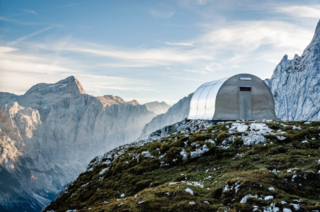 """13 Epic Alpine Retreats We're Swooning Over - Photo 5 of 13 - Based on the 1936 design of a bell-shaped metal alpine shelter, """"Bivak II na Jezerih"""" was updated for modern use with an interior outfitted in wood and designed to accommodate the area's harsh climate: hurricane-force winds, several meters of snow, and general water and sun exposure. The shelter can accommodate up to six people with a folding table, overlapping bench, and other multipurpose pieces."""