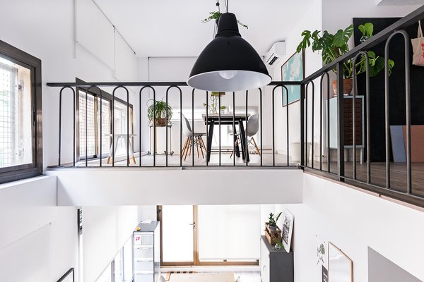 "The space is divided into two levels, a white and spacious first floor, full of natural light, presided by a large table that invites to a conversation, and a cozy attic that serves as a study. Photo  of ""La Agencia"" a new brand workspace plenty of design and inspiration modern home"