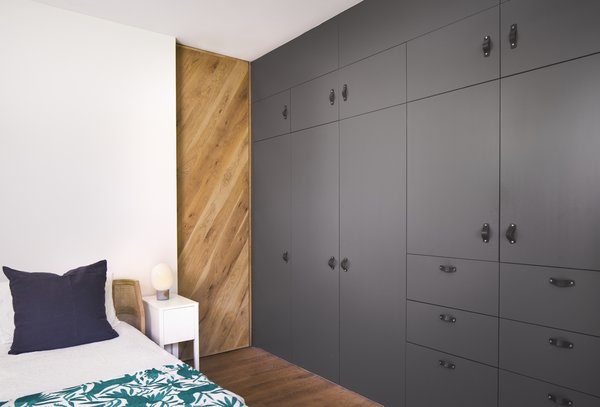 Full height closet storage cabinets and post oak pocket door. Photo 16 of Airole Way Residence modern home