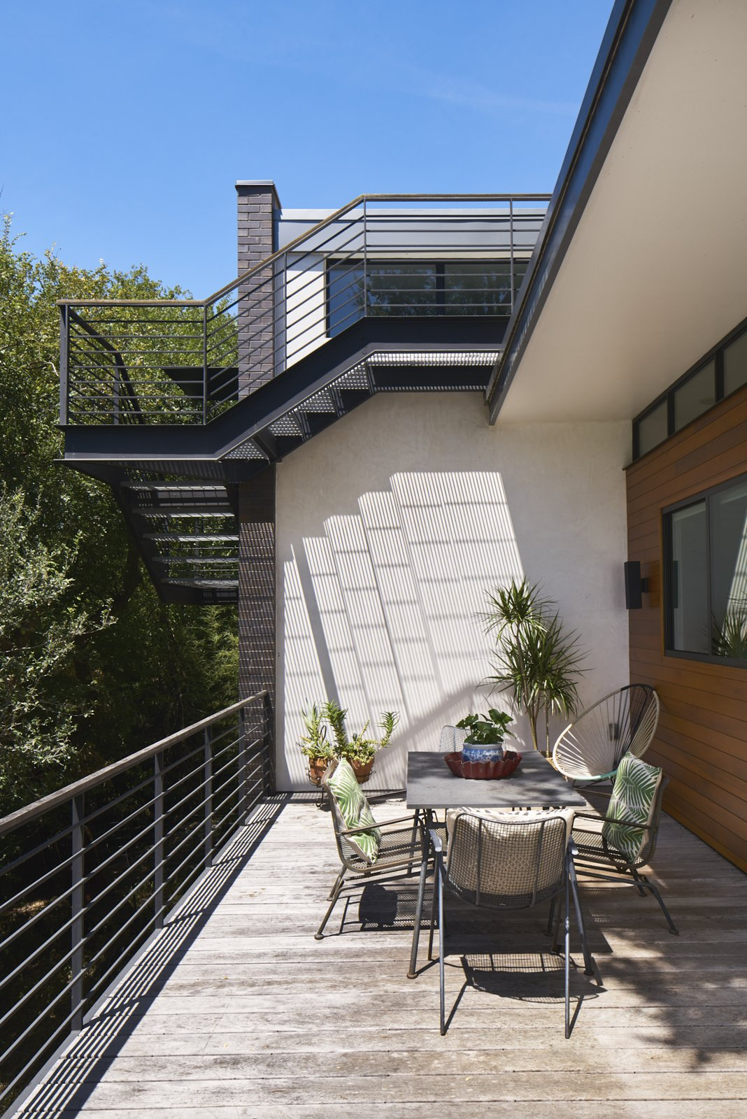 Cantilevered stair to roof deck overlooking patio.