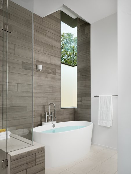 Master bathroom with marble tile and custom steel corner window. Photo 15 of Vance Lane Residence modern home