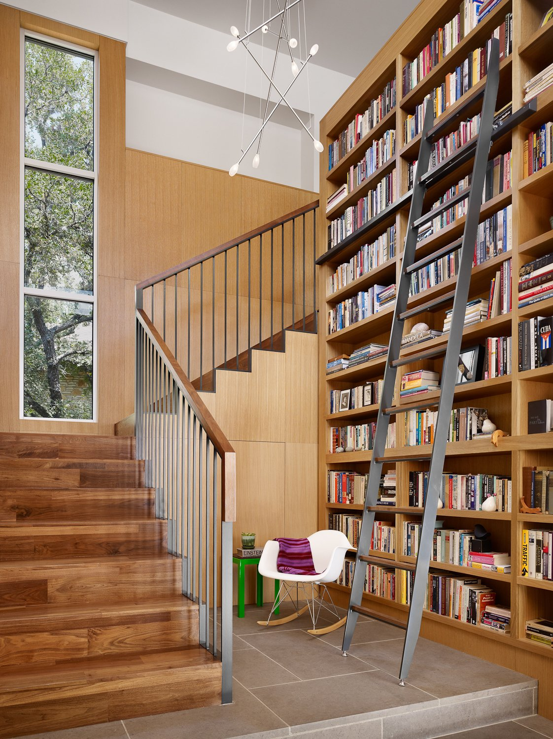 Stair and Library reading nook and custom steel library ladder.  Vance Lane Residence by Jamie Chioco