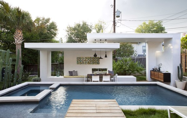 Modern home with outdoor, hardscapes, garden, gardens, back yard, trees, shrubs, grass, large pool, wood patio, porch, deck, small patio, porch, deck, and hanging lighting. Photo  of Winflo Pool & Cabana
