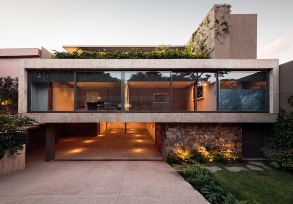 Modern home with outdoor, front yard, shrubs, grass, and landscape lighting. CAUCASO Photo  of Caucaso