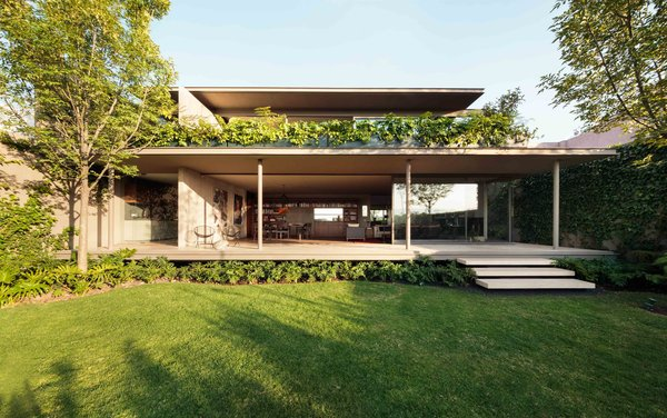 Modern home with outdoor, back yard, trees, grass, large patio, porch, deck, shrubs, and wood patio, porch, deck. CAUCASO Photo 3 of Caucaso
