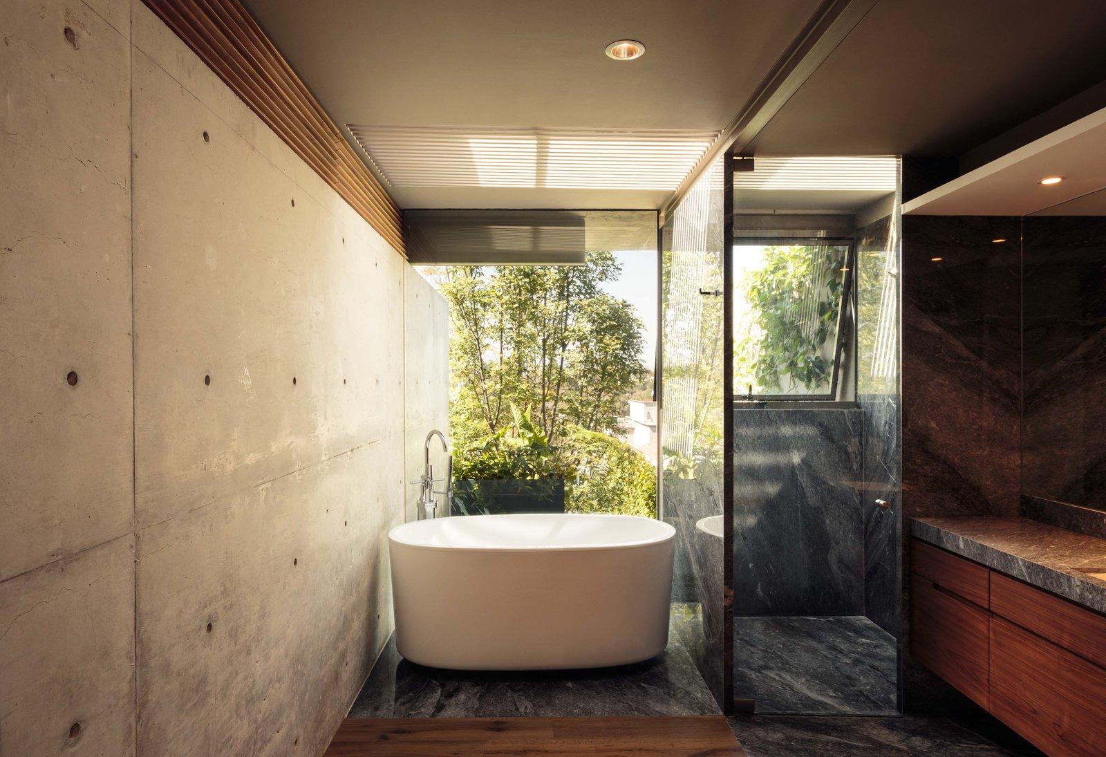 CAUCASO Tagged: Bath Room, Granite Counter, Medium Hardwood Floor, Soaking Tub, Enclosed Shower, Freestanding Tub, Recessed Lighting, and Concrete Wall.  Caucaso by Jose Juan Rivera Rio